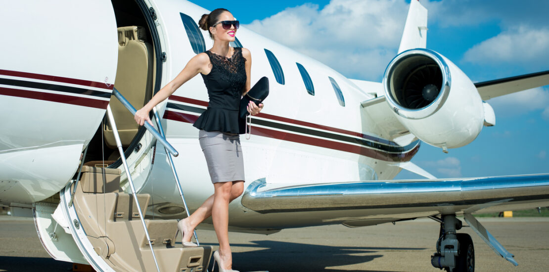 Young sensual businesswoman leaving private jet airplane upon arrival at travel destination.